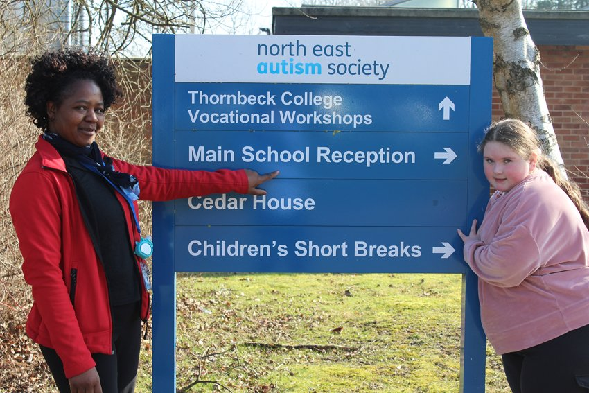 Adeline and student at aycliffe entrance sign
